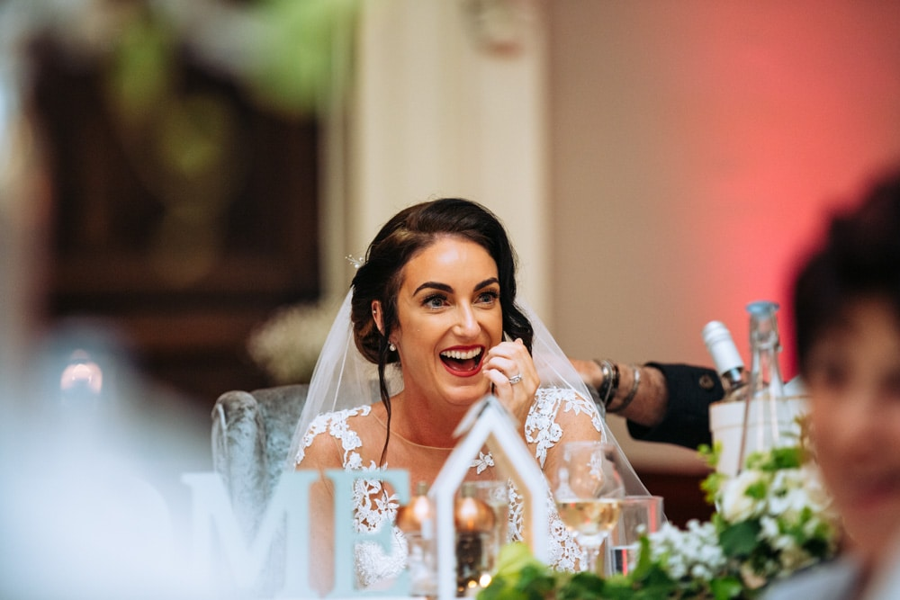 The bride laughing during speeches at Knutsford Courthouse