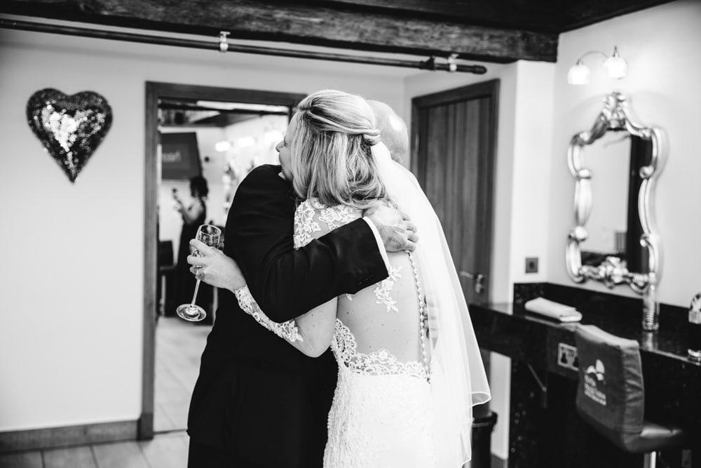 dad hugging bride at heaton house farm