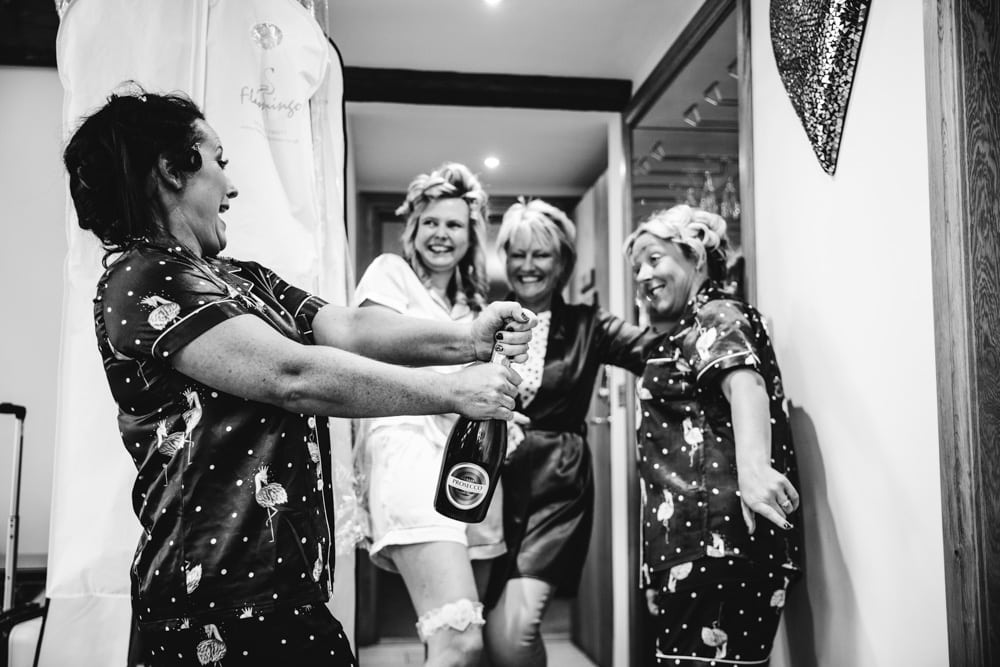 bridesmaids having fun opening bubbles at heaton house farm