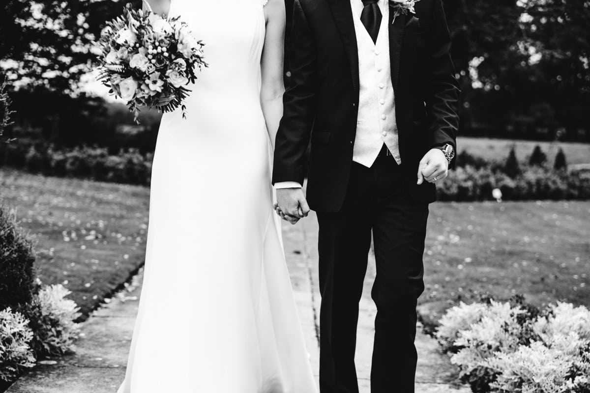 bride and groom holding hands at thornton hall hotel
