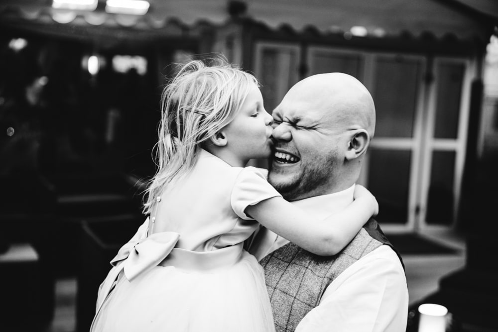 little girl kissing daddy at a wedding