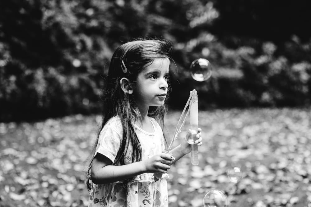 nerea playing with bubbles in her worsley garden