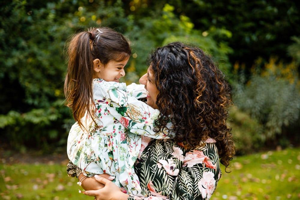 mum and daughter hug in a garden in worsley