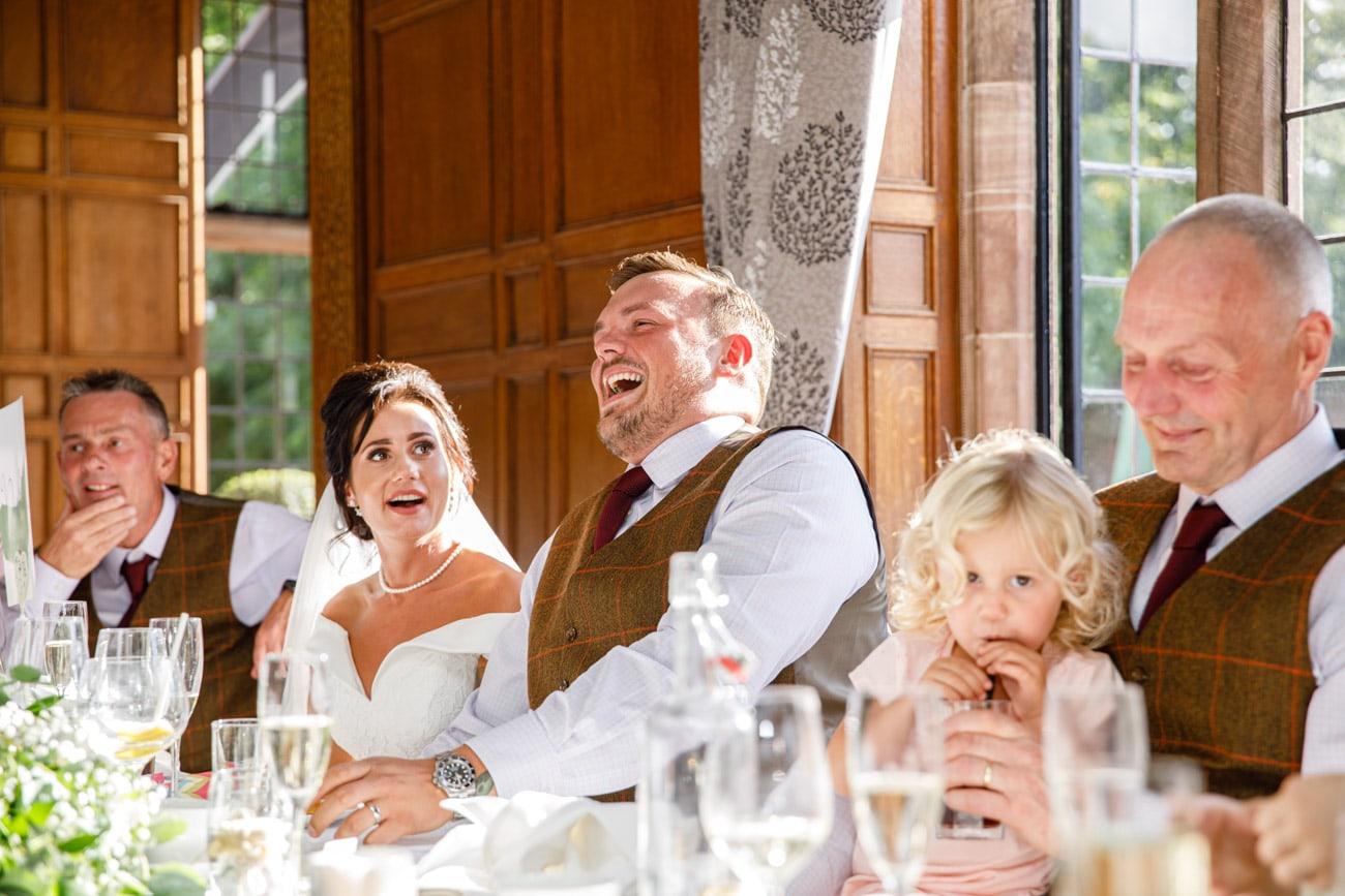groom laughing during wedding speech