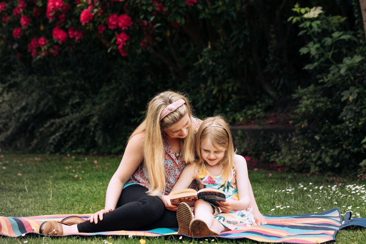 Mum and Daughter reading in a park