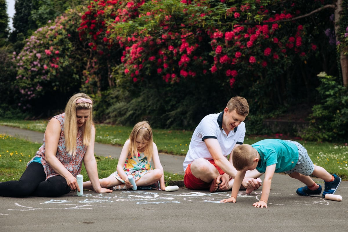 Family writing with chalk