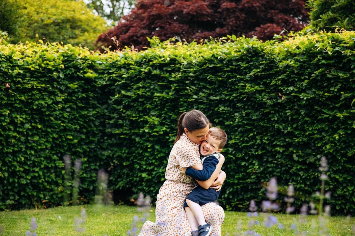 Mum cuddles son in garden